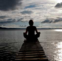 Woman meditating on dock photo